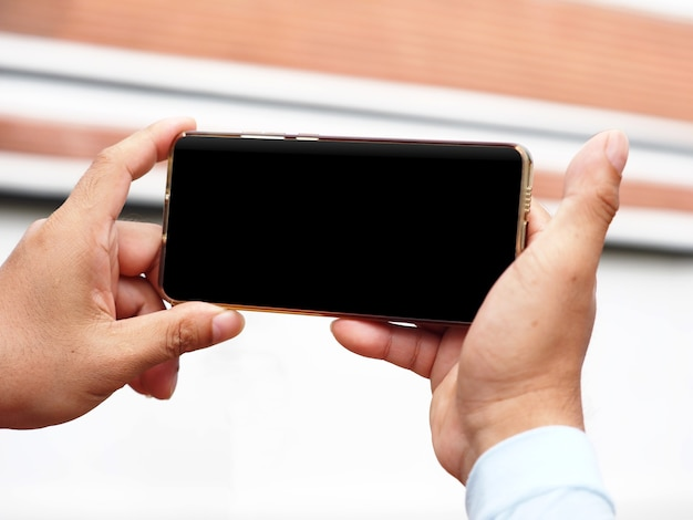 Selectief gerichte hand met mobiele telefoon met leeg zwart scherm, zoeken naar informatie, verbinding met mensen, online studeren