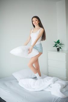 Selectief leuk meisje in de ochtend op een wit bed met een pillowon het mooie donkerharige glimlachende meisje die witte pyjama's dragen die in het bed liggen die ons bekijken die over mirakelavond denken. bovenaanzicht