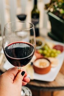 Selectief verticaal close-upschot van een wijfje dat een wijnglas houdt dat met donkerrode wijn wordt gevuld
