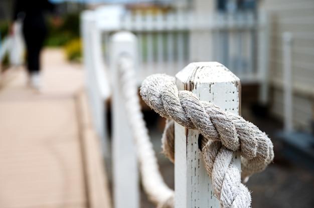 Selectieve aandacht close-up shot van een touw vastgebonden op een houten paal van een oude vuurtoren