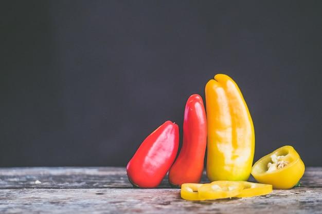 Selectieve aandacht close-up shot van gele en rode chili pepers in een bos op een houten oppervlak