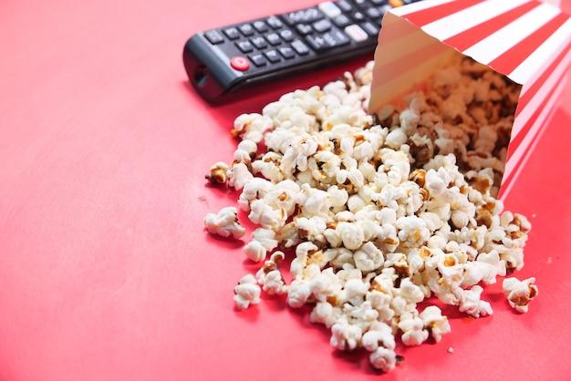 Selectieve aandacht. close-up van popcorn en tv-afstandsbediening op rode achtergrond