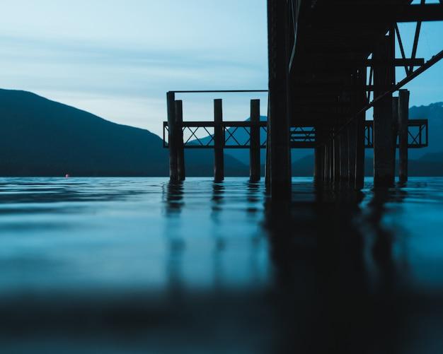 Selectieve aandacht die van een weg over het water met bergen in de verte is ontsproten