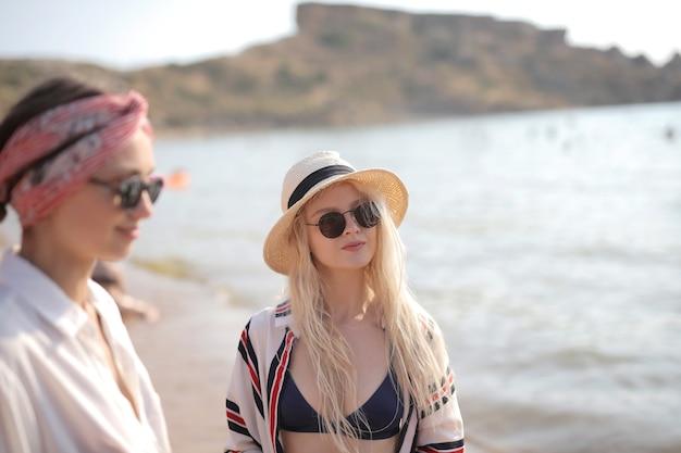 Selectieve aandacht die van twee jonge vrouwen met een bril op het strand is ontsproten