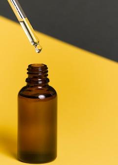Selectieve aandacht. een glazen potje met een pipet. binnenin zit een cosmetische biologische olie voor de huid van het gezicht en lichaam. op een geelgrijze papieren achtergrond. copyspace