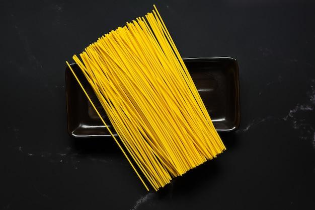 Selectieve aandacht gele noedels in gerecht. voedsel en kopieer de ruimte. rauwe pasta. rijstvermicelli en ruimte.