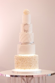 Selectieve aandacht. grote koninklijke taart in witte kleur versierd met zilveren details en witte crème op een luxe bruiloft. dessert na het feestelijke diner van de bruid en bruidegom.