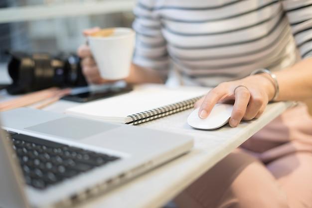Selectieve aandacht hand van vrouwelijke student klikken muis start werken huiswerk project
