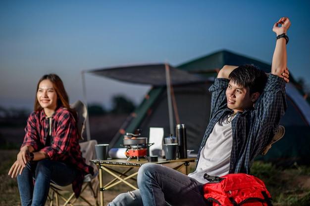 Selectieve aandacht handsomman zittend op een stoel en strekkende armen in de buurt van zijn vriendin aan de voorkant van de campingtent, ze glimlachen van geluk en frisheid wanneer ze ontspannen in de natuur.
