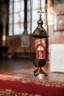 Selectieve aandacht. het wierookvat van de priester hangt aan een oude muur in de orthodoxe kerk. koperen wierook met brandende kolen erin. service in het concept van de orthodoxe kerk. aanbidding