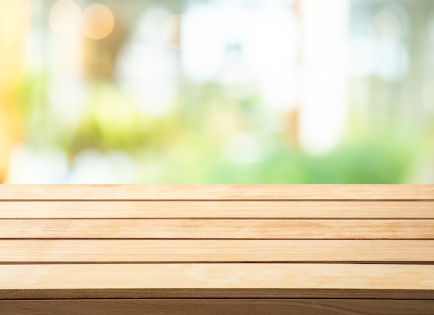 Selectieve aandacht. houten tafelblad op abstracte glazen wand achtergrond wazig.