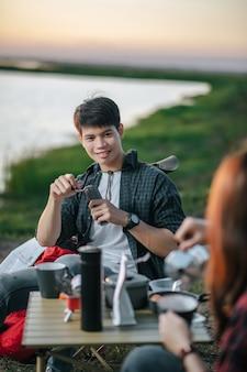 Selectieve aandacht, knappe man die verse koffiemolen maakt, vrolijk jong backpackerpaar zit aan de voorkant van de tent in de buurt van meer met koffieset tijdens het kamperen op zomervakantie