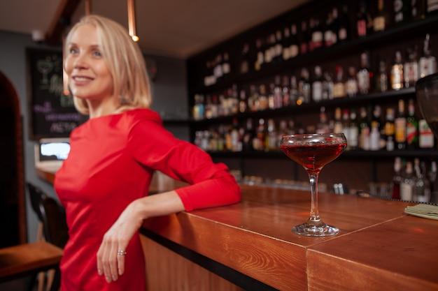 Selectieve aandacht op cocktailglas op de voorgrond, vrouw in rode jurk ontspannen aan de bar op de achtergrond, kopie ruimte