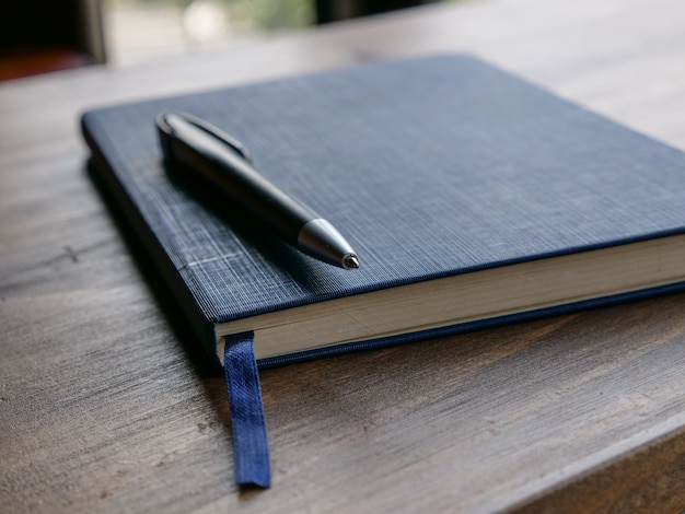 Selectieve aandacht op pen en notitieblok op houten bureau