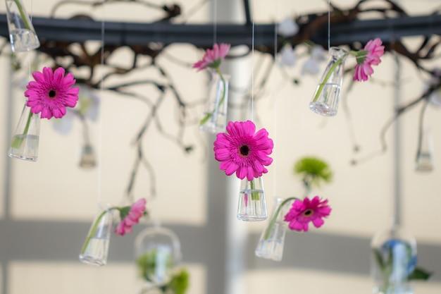 Selectieve aandacht roze gerbera madeliefjebloemen in glazen flessen hangen aan de lucht