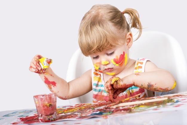 Selectieve aandacht shot van een klein meisje schilderen en spelen