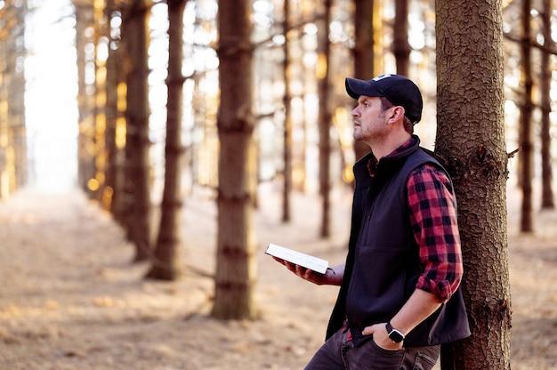 Selectieve aandacht shot van een man met een boek poseren in een bos