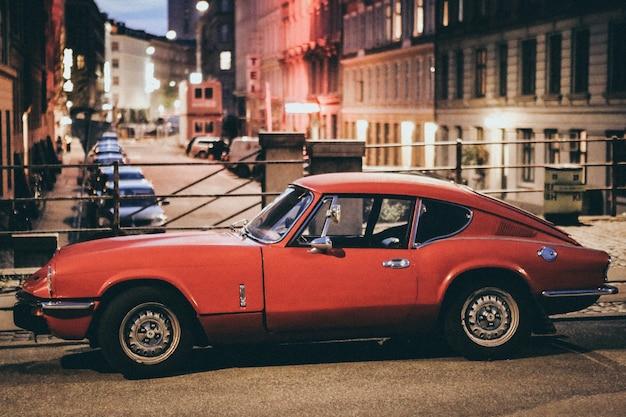 Selectieve aandacht shot van een rode auto van porsche geparkeerd in de buurt van gebouwen in een onscherpe achtergrond