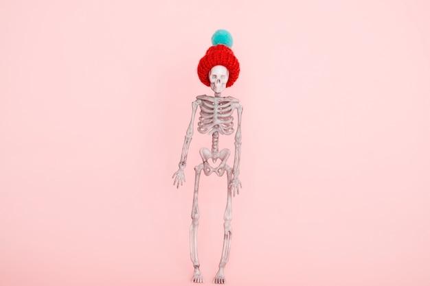 Selectieve aandacht skelet met schattige gebreide muts op een roze achtergrond