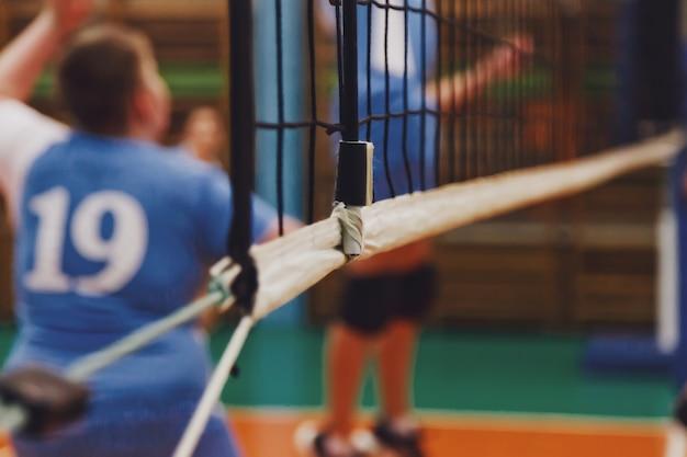 Selectieve aandacht: sport afbeelding van volleybalspel en net in een oude lege sporthal. achtergrond voor teamvolleybalspel. concept van het krijgen van sport, een gezonde levensstijl en teamsucces. ruimte kopiëren