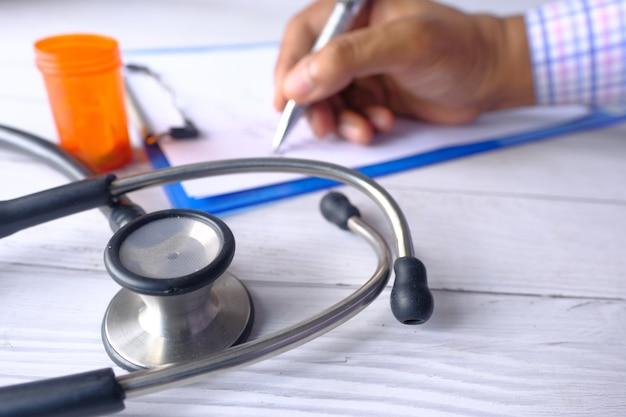 Selectieve aandacht. stethoscoop, wit vel papier en pillen op kliniek tafel.
