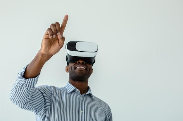 Selectieve aandacht van de hand van positieve afro-amerikaanse man vr-bril testen