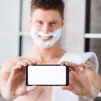 Selectieve aandacht van een man met scheerschuim op zijn gezicht met blanco witte slimme telefoon naar de camera