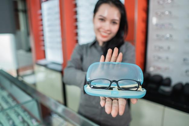 Selectieve aandacht van glazen in lenzenvloeistof doos met copyspace tegen de achtergrond van een mooie vrouw die lacht in een opticien