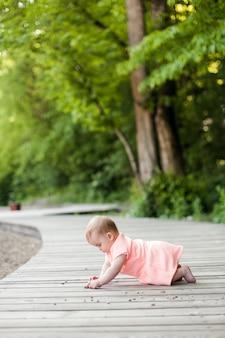 Selectieve aandacht van happy 6 maanden kleine jongen draagt roze jurk kruipen op het gras en spelen