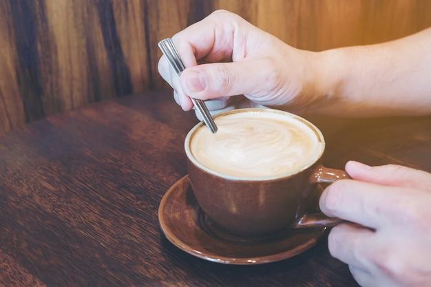 Selectieve aandacht van man roeren koffie