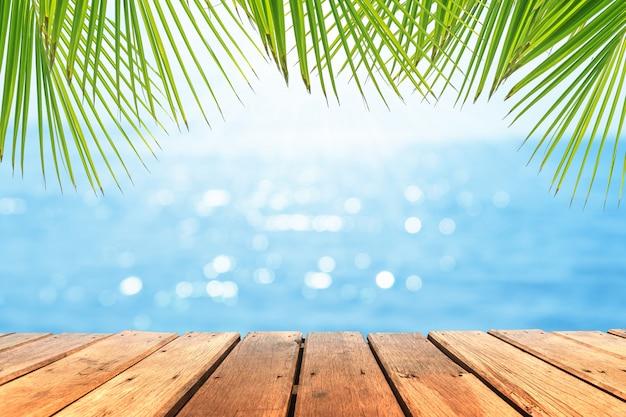 Selectieve aandacht van oude houten tafel met prachtige strand achtergrond voor weergave van uw product.