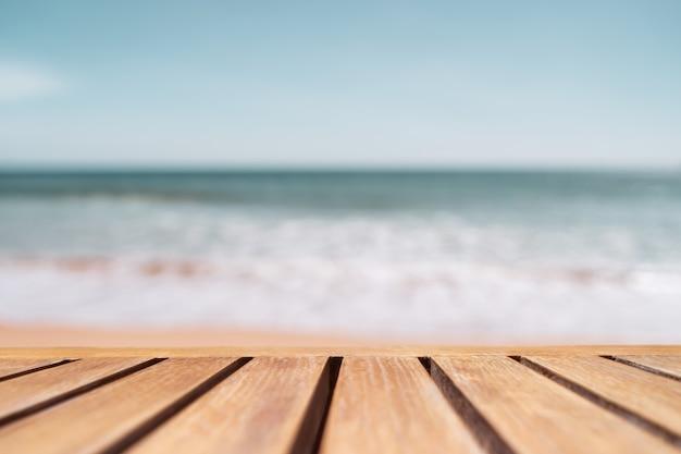 Selectieve aandacht van oude houten tafel met prachtige strandachtergrond om uw product weer te geven.