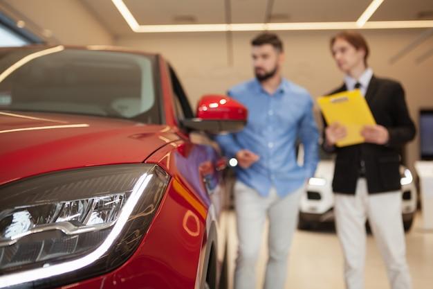 Selectieve aandacht voor autolampen, autodealer en mannelijke klant praten over achtergrond bij autodealer