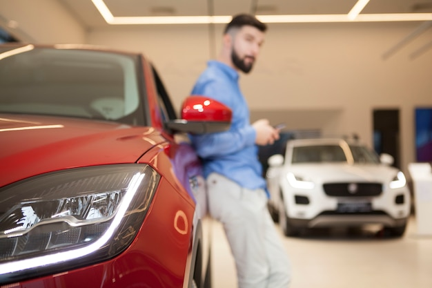 Selectieve aandacht voor autolichten, man met behulp van slimme telefoon, leunend op een auto op de achtergrond.