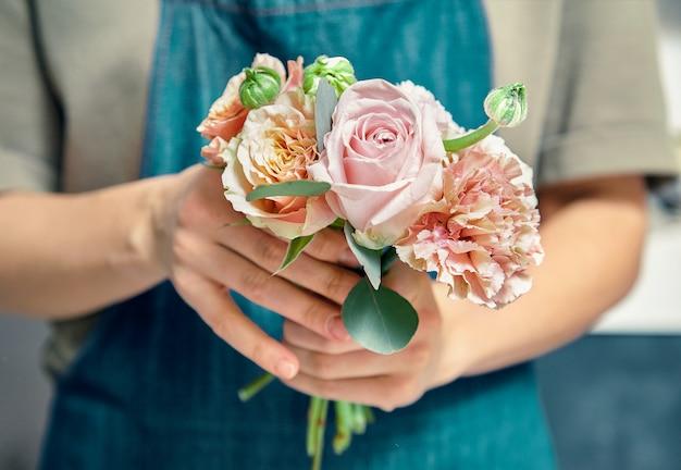 Selectieve aandacht voor bloemboeket in vrouwelijke handen. bloemistvrouw die bos maken bij winkel. bloemenwinkel, business, verkoop en bloemisterij concept. kopieer ruimte voor ontwerp