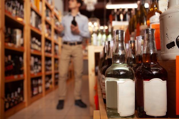 Selectieve aandacht voor de whiskyflessen, man winkelen voor sterke drank in de supermarkt op de achtergrond