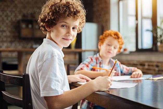 selectieve aandacht voor een jongen met krullend haar die in de camera kijkt met een lichte glimlach op zijn gezicht terwijl hij aan een eettafel zit en zijn vrije tijd doorbrengt met een broertje.