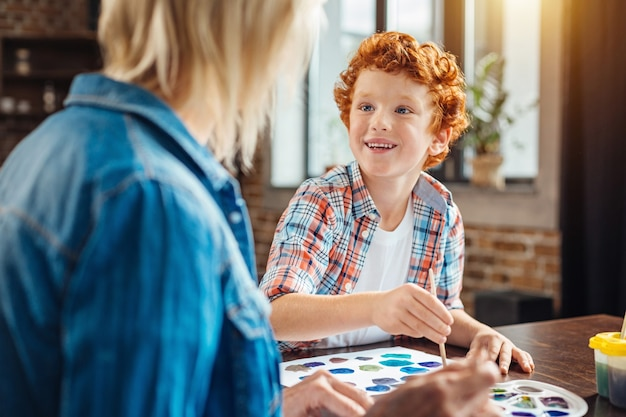 Selectieve aandacht voor een opgewonden jongen die naar zijn grootmoeder glimlacht terwijl hij zowel een aangenaam gesprek voert als schildert aan een tafel.