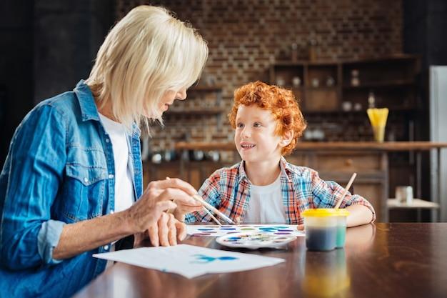 Selectieve aandacht voor een schattig kind met krullend haar dat naast zijn grootmoeder zit en haar een interessant verhaal vertelt terwijl ze allebei aan een tafel aan het schilderen zijn.