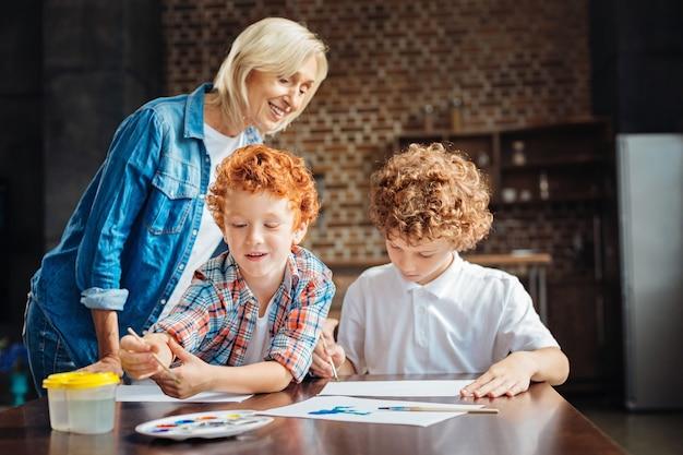 Selectieve aandacht voor een schattige roodharige jongen die een penseel vasthoudt en een aquareltint kiest terwijl hij naast zijn oudere broer in het huis van hun grootmoeder schildert.