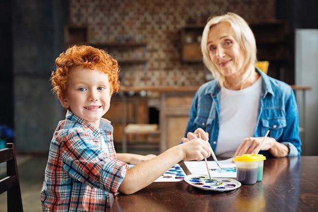 Selectieve aandacht voor een schattige roodharige jongen die zich omdraait en poseert voor de camera met een opgewonden glimlach op zijn gezicht terwijl hij thuis schildert met zijn liefhebbende grootmoeder.