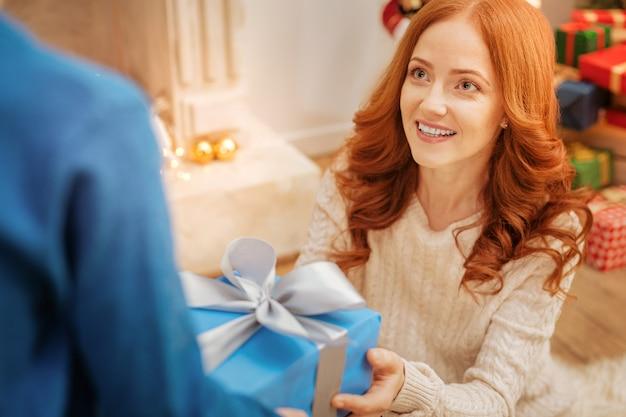 Selectieve aandacht voor een verbaasde vrouw die met ogen vol verbazing naar haar zoontje kijkt terwijl ze een kerstcadeau van hem ontvangt.