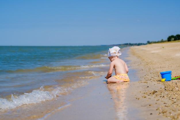 Selectieve aandacht voor peuter meisje zittend in het water op het zand op het strand het kind speelt met speelgoed achteraanzicht op het hoofd is een witte bandana sjaal ondiepe scherptediepte gelukkige jeugd