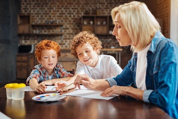Selectieve aandacht voor slimme broers met krullend haar die aan een tafel zitten en aquarellen kiezen op een palet terwijl ze aan hun nieuwe meesterwerk werken.