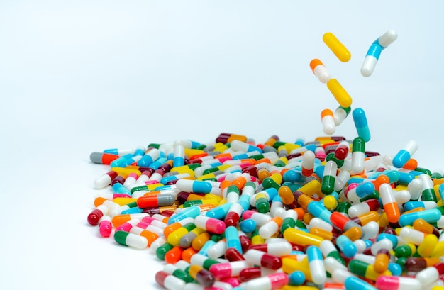Selectieve aandacht voor stapel antibiotische capsule pillen. kleurrijke antibiotica capsules pil vallen op witte tafel.