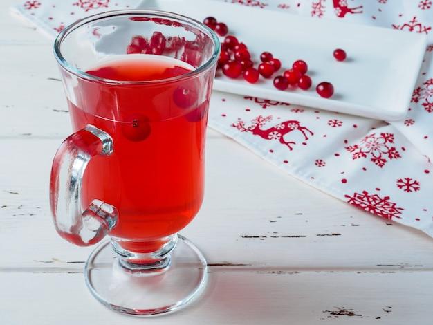 Selectieve aandacht voor veenbessen in een fris drankje in een glazen beker. bessen op een witte rechthoekige keramische plaat en een servet met een nieuwjaarsornament.