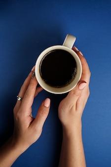 Selectieve aandacht, vrouwelijke handen die een mok zwarte thee op een blauw houden