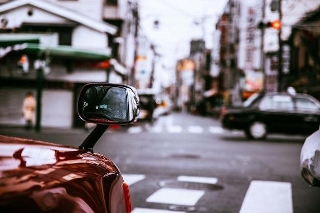 Selectieve close-up die van de zijspiegel van een rode auto op onscherp is ontsproten