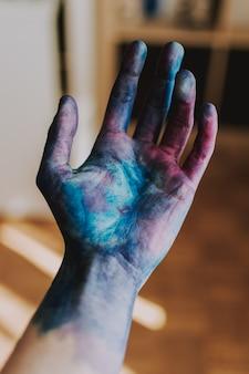 Selectieve close-up shot van iemands palm in blauwe en roze verf