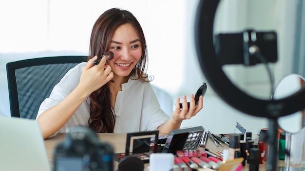 Selectieve focus op camera, jong en mooi aziatisch meisje laat zien hoe je een gezichtsborstel met een glimlach en blij naar de camera kunt gebruiken tijdens uitzendingen van video-opnames over cosmetica-inhoud en beoordeling.